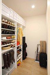 玄関クロークは、靴やコート、べビーカー、ゴルフバッグ、掃除道具などをしまえる大型収納。(施工例写真)