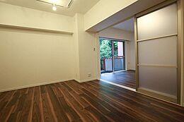 床のウォルナット色とバルコニーから見える緑が映えるお部屋です。