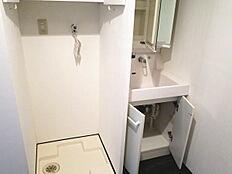 収納棚の奥に洗濯機置場(洗濯パン)と洗面化粧台が設置されています。洗面もお湯が使えます。
