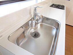 リフォーム済キッチンのシンクの写真です。キッチン前面の窓から光が入って、手元が明るいキッチンです。浄水器内蔵水栓なので、シンク周りに場所を取りません。