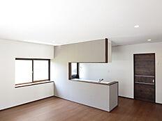 リフォーム後写真対面キッチンのあるリビングは、床を重ね張りして、壁・天井のクロスを張り替えました。カウンター部分にアクセントクロスを使用し、照明をダウンライトに交換しました。