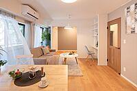 居間(木目調の暖かみのある床材、グレーベージュのアクセントクロスで落ち着いた空間を演出しました。)