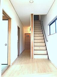 床・階段と統一感のある明るい玄関〜廊下。