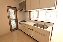 便利な勝手口を設置。大型の引き出しと床下収納、吊戸棚がございます。散らかりがちなキッチンに嬉しい収納力です。
